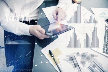 Banker manager working process.Photo analyst trader work market graphs.Using electronic devices.Graphic icons,worldwide online stock exchanges interfaces on screen.Business project startup.Film effect