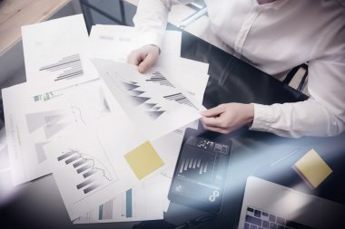 Risk management work process.Photo banker holding statistics document hands.Using electronic devices.Work graphics,stock exchanges reports screen tablet.Business project startup.Horizontal,film effect