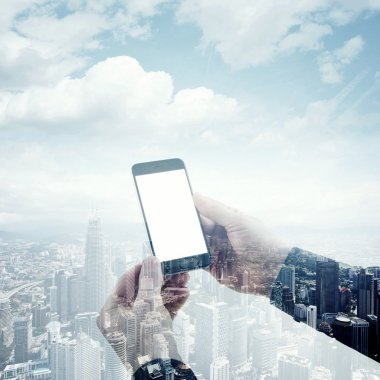 Double exposure photo modern smartphone holding male hands. Panoramic view contemporary city and clouds background. White blank screen ready for your business information.Square mockup.