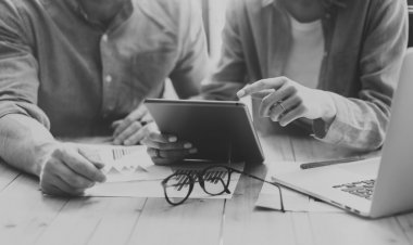Coworkers team brainstorming process modern loft.Project producer reading report tablet,glasses wood table.Young business crew working startup studio.Using Laptop.Blurred,film effec. Black White