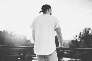Photo Bearded Muscular Man Wearing Blank t-shirt, snapback cap and shorts in summer time. Green City Garden Park Sunset Background. Back view. Horizontal Mockup.Black White