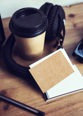 Closeup Stack Blank Kraft Paper Business Card Mockup Wood Table Background.Take Away Coffee Cup Coworking Studio.Modern Headphones Portable Sunglasses Interior Cafe.Vertical Lifestyle Mock Up Objects.