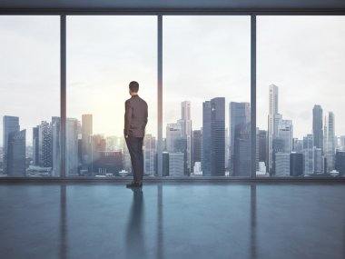 Businessman  in office and looking at city