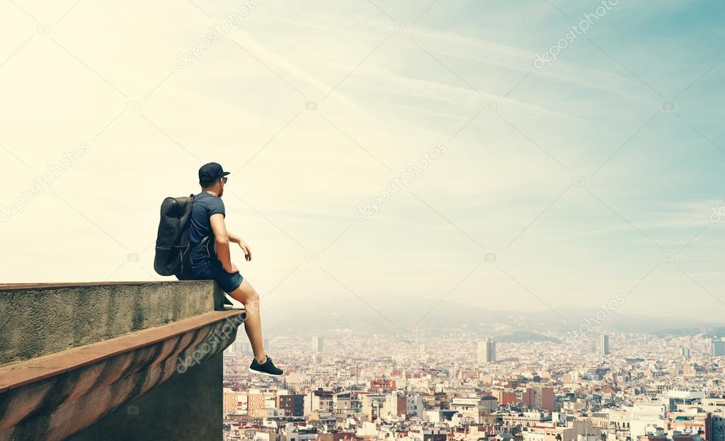 Young man is sitting on a roof