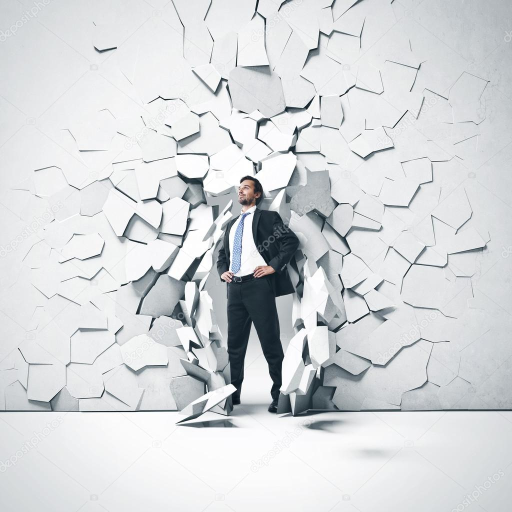 Young businessman breaking trough a wall