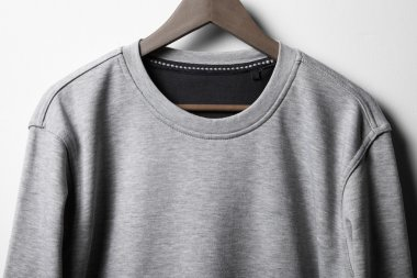 Grey jumper hanging on white wall