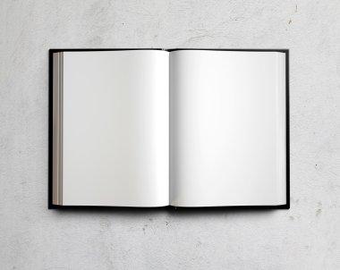 Open white textbook on concrete
