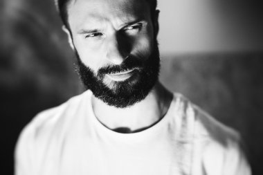 BW portrait of a bearded man wearing white tshirt on the blure background
