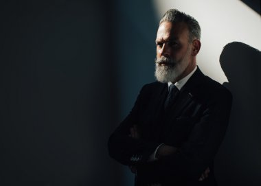 Portrait of stylish bearded man wearing trendy suit and stands against the wall. Horizontal