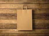 Řemeslo nákupní tašku na dřevěné pozadí. V centru pozornosti. Vodorovně. 3D vykreslování