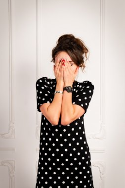 Brunette woman in a black dress covered her face with her hands
