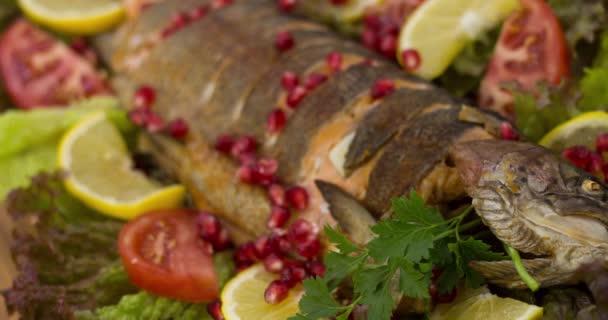 Sült hal pisztráng különböző zöldségekkel és gyógynövényekkel, citrom étellel, gránátalmamag
