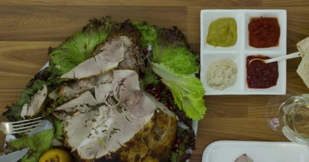Húsipari termékek fehér tányéron, természetes étel. Különböző ízletes ételek egy fa asztalon.