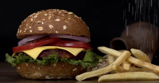 Zblízka pohled na lahodný čerstvý burger a padající hranolky