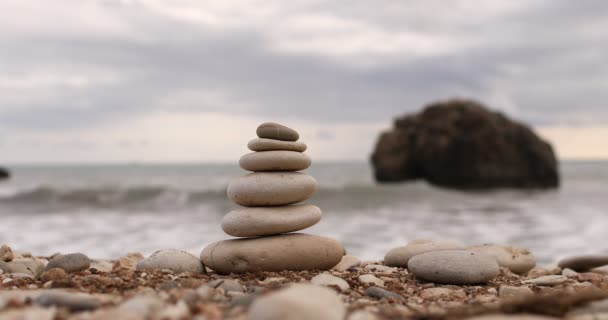 4k video of Pyramid stones on the seashore on a sunny day on the blue sea background. Happy holidays. Pebble beach, calm sea, travel destination. Concept of happy vacation on the sea
