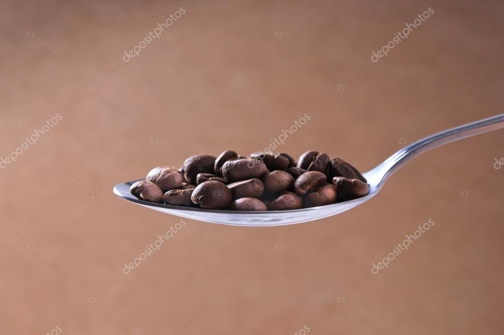 Licht Gebrande Koffiebonen : Stalen lepel van gebrande koffiebonen op licht bruin achtergrond