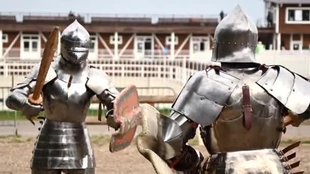 Two medieval knights in full heavy armor reenact a battle on tournament