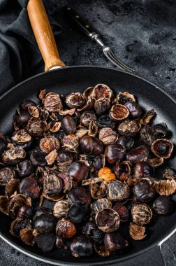 Roast grilled chestnuts on a wooden table. Black background. Top view.