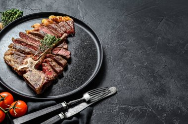 Grilled Porterhouse steak on a plate. Cooked beef meat. White wooden background. Top view. Copy space.