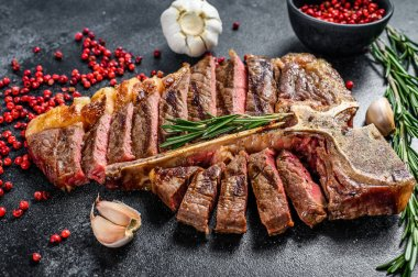 Grilled T-bone steak. Cooked tbone beef. Black background. Top view