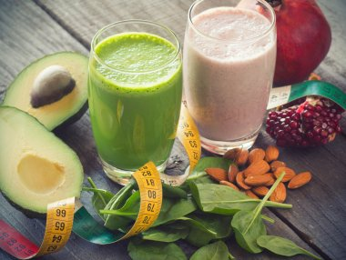 Two fresh blended fruit smoothies made with avocado, pomegranate, spinach and almonds