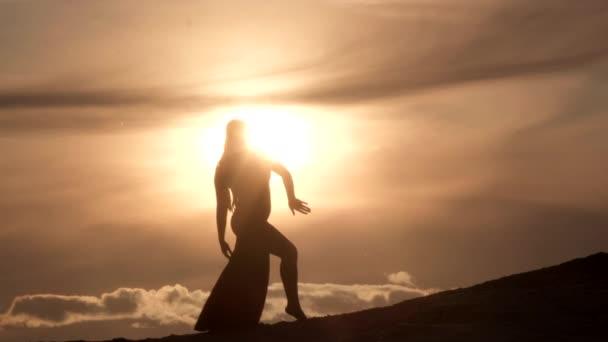 Krásná mladá žena tančí orientální břicho tanec na písečném kopci při západu slunce. Silueta.