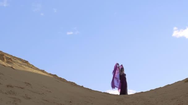 Eine schöne Frau in orientalischer Tracht steht bei Sonnenuntergang auf einem sandigen Hügel. Ein transparenter roter Schleier über dem Kopf flattert im Wind. Extremer Weitschuss.