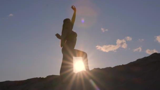 Krásná mladá žena tančí tanec na Blízkém východě na písečném kopci při západu slunce. Silueta.
