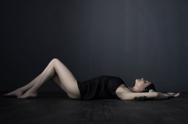 Sexy dressed woman laying down on a dark wooden floor