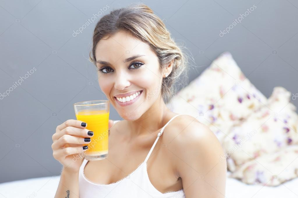 Relaxed woman drinking orange juice at home in bedroom