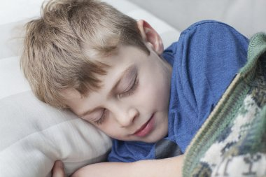 Little boy sleeping on sofa in room