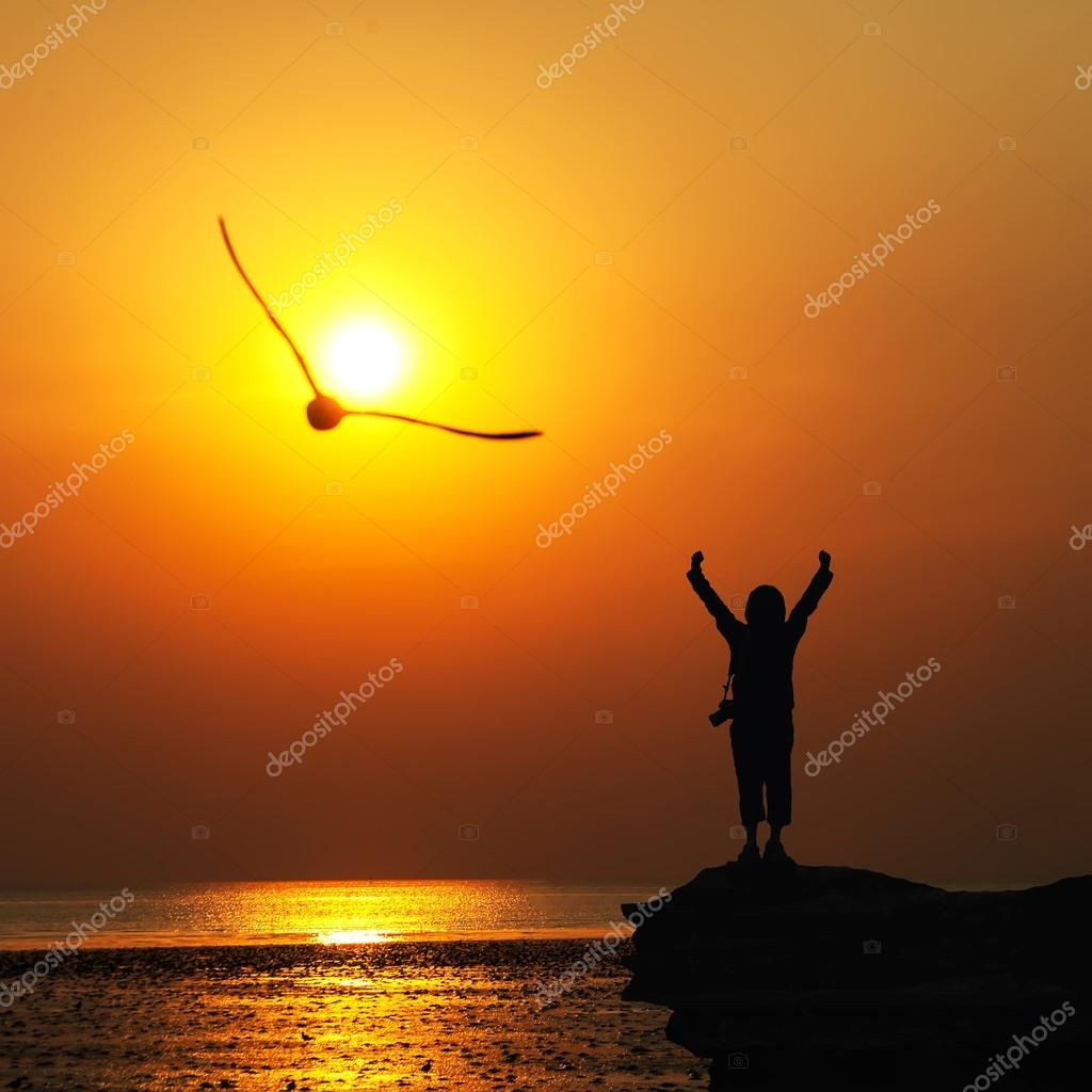 Silhouette of traveller with hands raised to birds flying in to