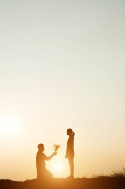 silhouette man kneeling marriage to his girlfriend on sunset bac