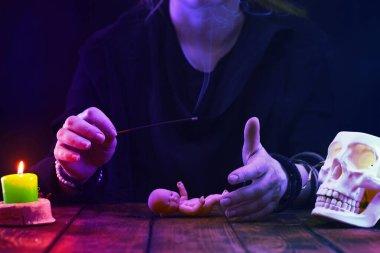 Falcı, cadı ya da kahin bir bebek üzerinde ayin yapar. Psişik okumalar ve kehanet kavramı. Neon ışıklı fotoğraf..