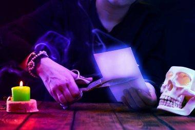 Falcı, cadı ya da kahin bir fotoğrafı büyük metal bir makasla keser. Psişik okumalar ve kehanet kavramı. Neon ışıklı fotoğraf..
