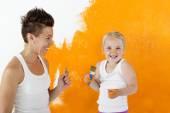Fotografie Mutter und Tochter malen zu Hause eine Wand