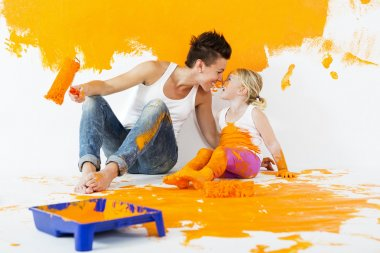 Mother and daughter painting a wall at home