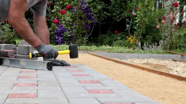 A construction worker installs concrete blocks for sidewalks in the courtyard of a country house.