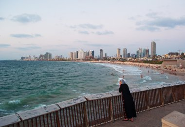Israel: a muslim woman at the promenade of Jaffa with view of Mediterranean Sea and Tel Aviv skyline