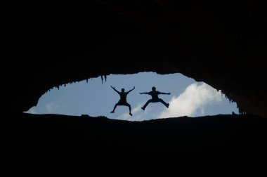 Two man jumping backlight at the entrance of the Hoq Cave, Homhil Plateau, Socotra Island, Yemen, Middle East