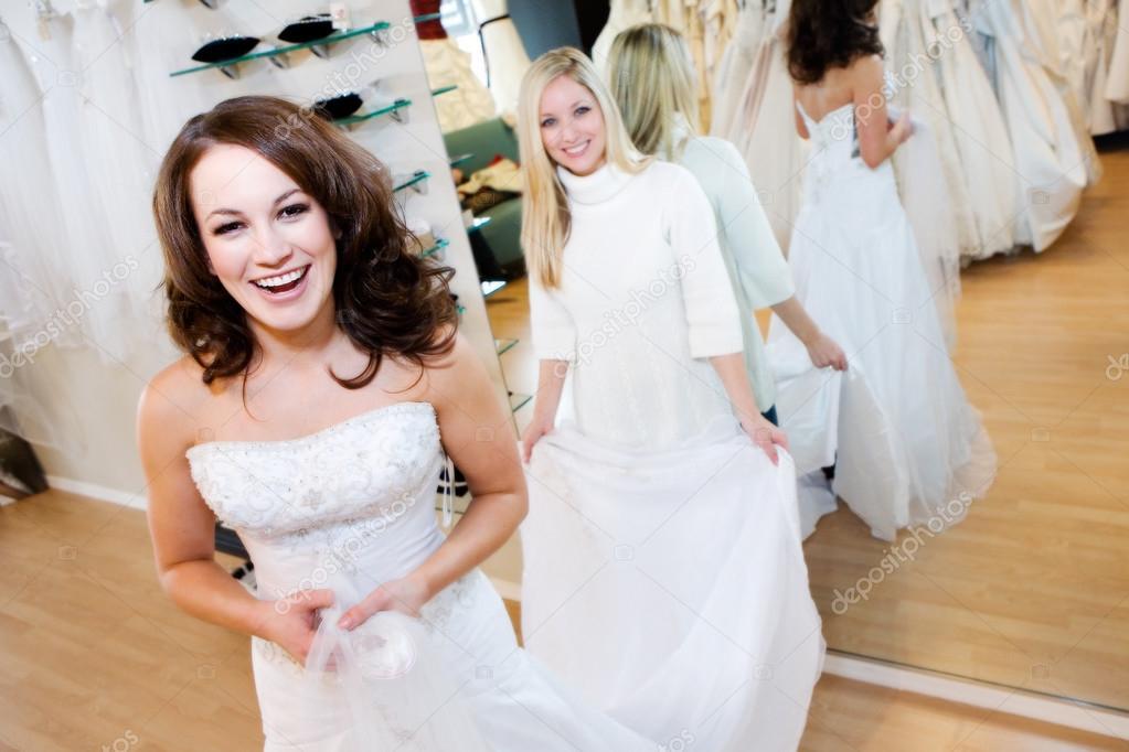 novia: mujer probandose el vestido de novia con ayuda de la