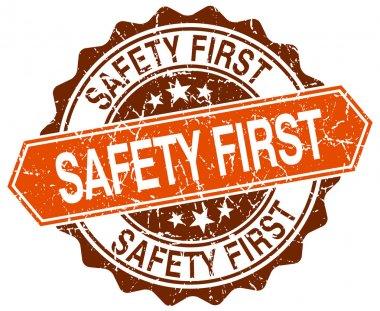 Safety first orange round grunge stamp on white