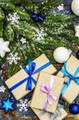 Vánoce nebo Nový rok dárky s věčně zelenými větvemi jedle, slavnostní koule, hvězdy a sněhové vločky. Ročník dřevěné desky pozadí v námořně modré tóny, pohled shora
