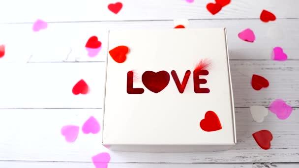a szív repül az ajándékdobozon a Szerelem szóval. ajándék fehér fa háttér Valentin nap.