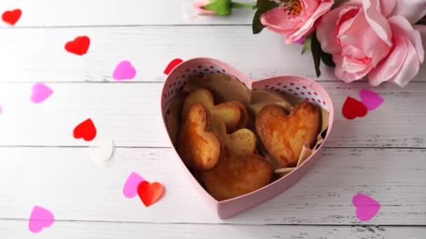 Sušenky ve tvaru srdce v modré krabičce na Valentýna a růžové růže se srdcem na bílém dřevěném stole, dámská ruka dává sušenku do krabice