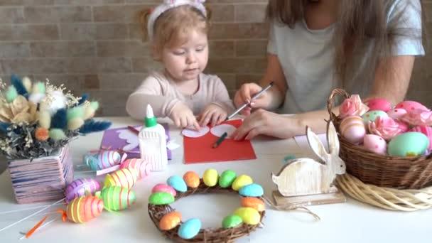 Atraktivní mladá žena s malou roztomilou dívkou se připravují na velikonoční oslavu. Máma a dcera nosí králičí uši se baví doma.