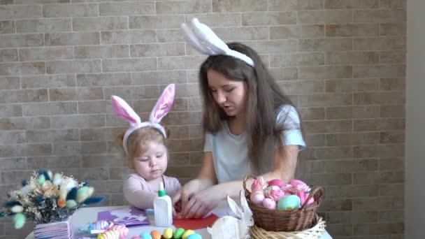 Matka a její dítě baví při malování velikonoční vajíčka