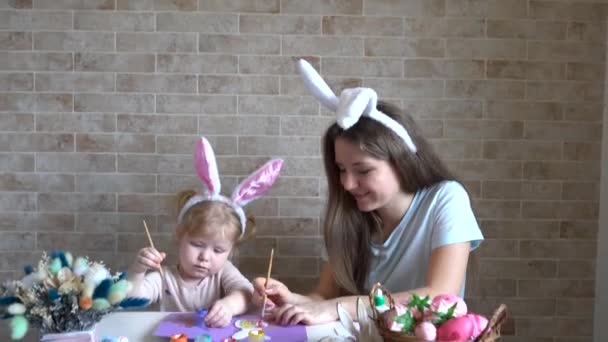 Attractive young woman with little cute girl are preparing for Easter celebration. Mom and daughter wearing bunny ears are having fun at home.