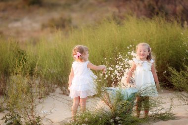 Little girls throws feathers at the beach
