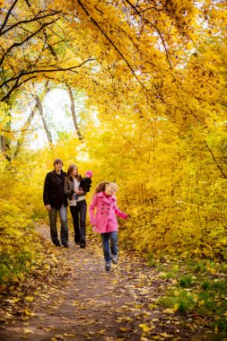 Family with children walking in the autumn park